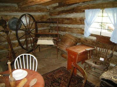 Log cabin downstairs interior, with a selection of historical items.