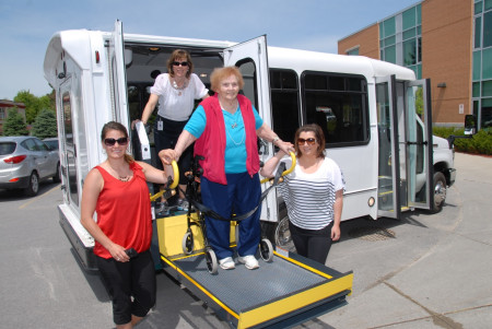 Fairview Manor's (FVM's) new bus features a lift with a remote control. Shown with the new bus are, from left, FVM Recreation Therapist (RT) and driver Ashley Charlebois, RT and driver Sheila Lefebvre, FVM resident Verna Wheeler and RT and driver Kayla Nichols.