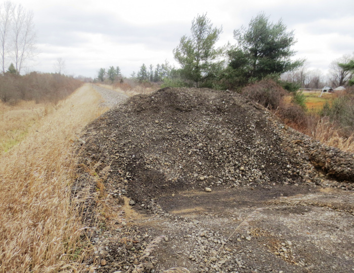 The once a continuous ribbon across the landscape, the railbed is now blocked by mounds of coarse aggregate.
