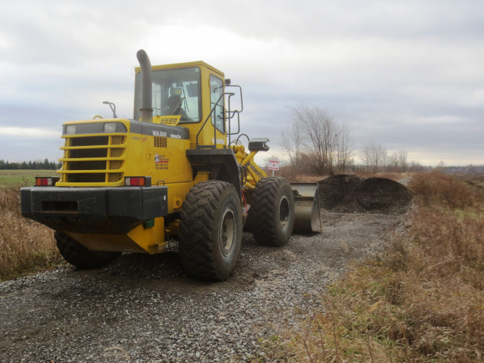 With rails, tie plates, spikes, and ties removed, it was easy work for a heavy machine to dig up the railbed and create obstacles to vehicular traffic.